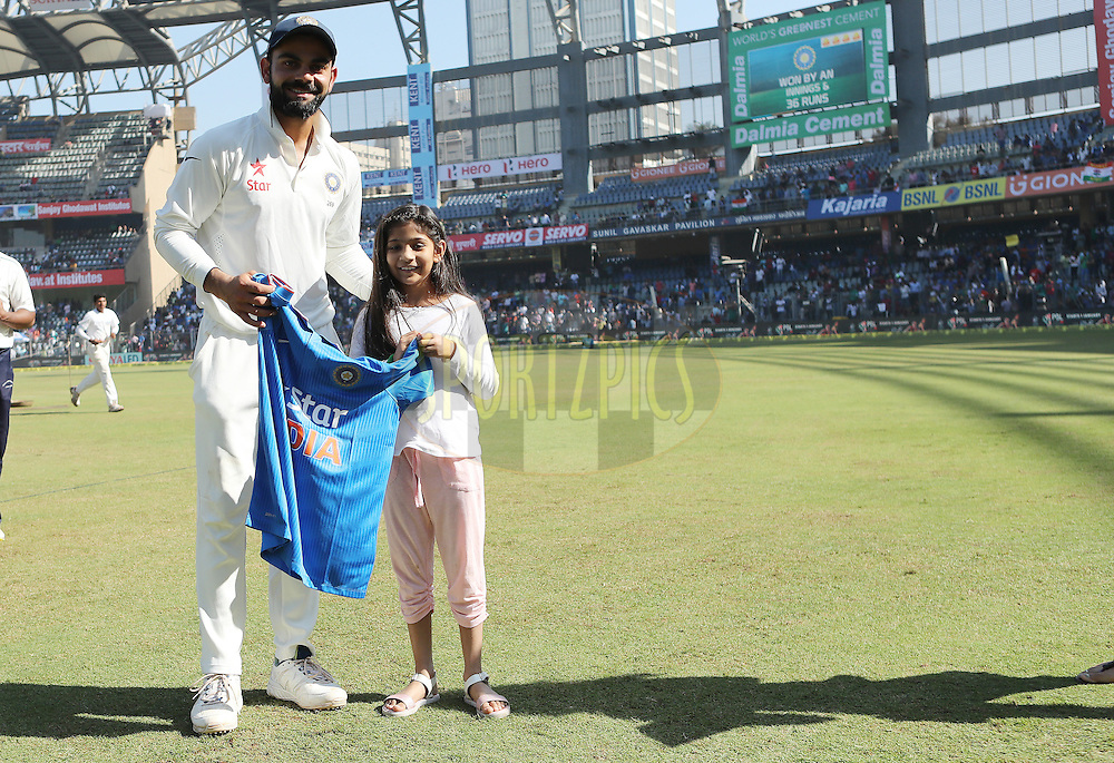 Virat Kohli Captain of India presents a young fan with an Indian jersey during day 5 of the fourth test match between India and England held at the Wankhede Stadium, Mumbai on the 12th December 2016.<br /> <br /> Photo by: Ron Gaunt/ BCCI/ SPORTZPICS