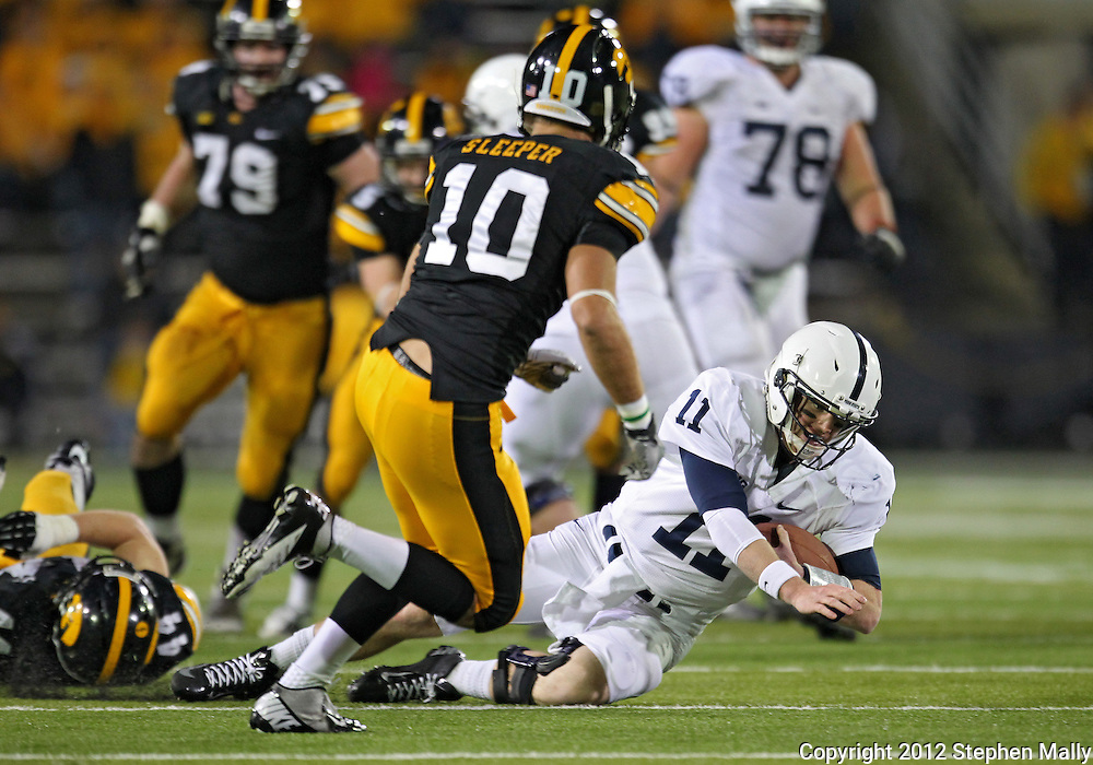 October 20 2012: Penn State Nittany Lions quarterback Matthew McGloin (11) slides as Iowa Hawkeyes defensive back Collin Sleeper (10) closes in during the second half of the NCAA football game between the Penn State Nittany Lions and the Iowa Hawkeyes at Kinnick Stadium in Iowa City, Iowa on Saturday October 20, 2012. Penn State defeated Iowa 38-14.