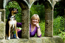 Young playful Black and Tan juvenile mongrel dog poses erect and alert looking through a ruined stone window beside his owner in Canon Hall Country Park <br /> <br /> 31 August  Copyright Paul David Drabble