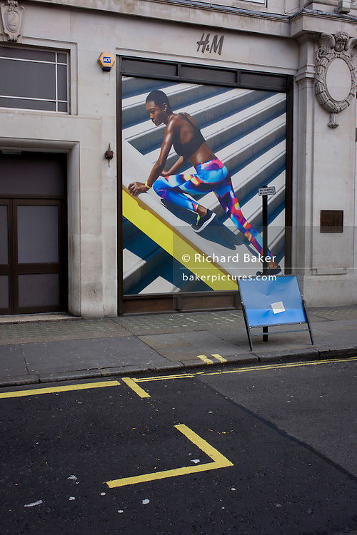 Stylish and athletic model on a billboard for clothing retailer H&M, in central London.