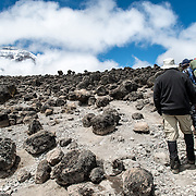 Hikers on the rugged apline desert trail on Mt Kilimanjaro Lemosho Route. These shots were taken on the trail between Moir Hut Camp and Lava Tower at approximately 14,500 feet. The summit is in the distance at left.