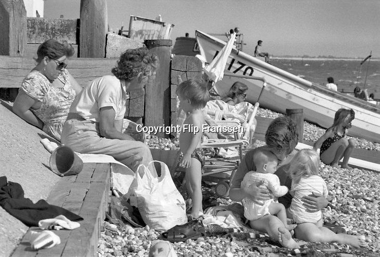 Engeland, England, 15-8-1990Straatbeeld. Reisreportage door het zuiden van Engeland. Strand en zee in de omgeving van Portsmouth . Badgasten  liggen op het strand in een baai van de noordzee, het kanaal . Krijtrotsen vormen de kust . Gezin met oma en jonge kinderen spelen op het strand.Foto: Flip Franssen