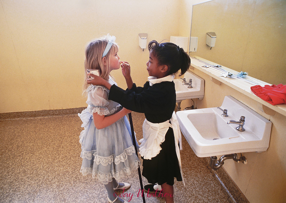 Kassie Smith, left, gets some help with her lipstick from fellow third-grader Marci Colbert before a Halloween parade at John Marshall Elementary School in Sacramento, California.