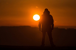 © Licensed to London News Pictures. 30/03/2016. Huddersfield UK. Picture shows a man watching this morning's sunrise from Castle Hill in Huddersfield as weather forecast's predict a sunny day for the county of Yorkshire. Photo credit: Andrew McCaren/LNP