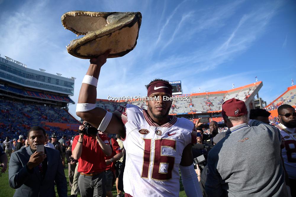 Florida State linebacker Jacob Pugh (16) hoists an alligator head on the field after an NCAA college football game against Florida Saturday, Nov. 25, 2017, in Gainesville, Fla. FSU won 38-22. (Photo by Phelan M. Ebenhack)