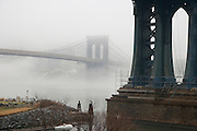 Brooklyn Bridge with Manhattan Bridges pillar in the foreground during a morning fog