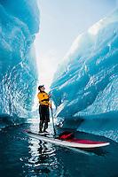 A man on stand up paddle board (SUP) explores an iceberg canyon on Bear Lake in Kenai Fjords National Park, Alaska.