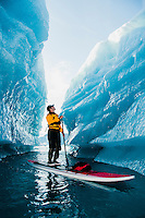 A man on stand up paddle board (SUP) explores an iceberg canyon on Bear Lake in Kenai Fjords National Park, Alaska.