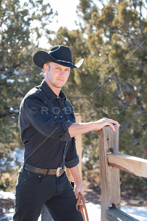 All American cowboy by a fence