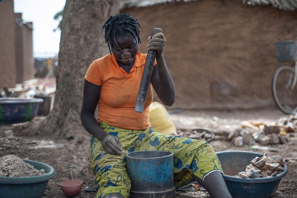 Rosine Kabore, frantuma pietre nel villaggio vicino alla miniera artigianale di Nobsin in Burkina Faso il 13 Maggio 2014. Riesce solitamente a lavorare 3 o 4 sacchi di pietre da ridurre in polvere alla settimana. Per ogni sacco di pietre frantumate riceve circa 1500 CFA francs (£1.85).