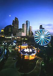Downtown Aquarium with lit ferris wheel and Houston, Texas skyline at night.