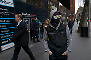 Man wearing a black mask across his face and sunglasses with cartoon eyes printed on the lenses, concealing his identity in London, England, United Kingdom. (photo by Mike Kemp/In Pictures via Getty Images)