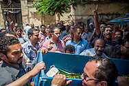 The body of a protestor killed during fighting in Cairo is carried into the city's morgue before a funeral later that day.