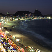 Praia de Copacabana at dusk. Copacabana beach, one of the world's most famous urban beaches at dusk with Sugar Loaf Mountain in the distance. The beach and hotel strip stretches for 1.5 miles (4km) from the Morro do Leme at the Northern end, to Arpoador. Copacabana beach, Rio de Janeiro,  Brazil. 20th July 2010. Photo Tim Clayton..