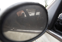 Looking at the reflection through the wing mirror of a vandalised and burnt out car in an inner city street,