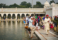 NEW DELHI, INDIA - CIRCA OCTOBER 2016: People worshiping in the pool of Gurudwara Bangla Sahi also known as Sikh house of worship in Delhi. This is oone of the most prominent Sikh gurdwara, often recognized by the pool inside its complex and the golden dome.
