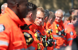 Members of the emergency services gather to observe a minute's silence near to Grenfell Tower in west London after a fire engulfed the 24-storey building on Wednesday morning.