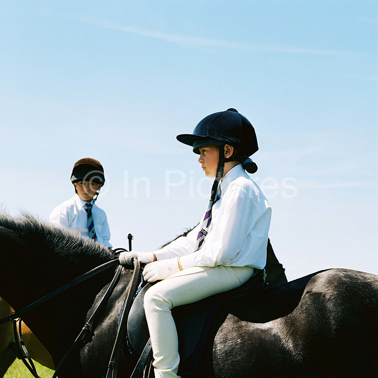 Farmer's children, Giles and Hannah Hawkins sitting on their horses at Pony Club, Exmoor, Somerset, UK