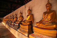 Cloister of Buddhas at Wat Phuttai Sawan - The main Khmer-style prang at Wat Phutthai Sawan is surrounded by a square  cloister enclosed by an outer wall, which along with the pillars inside supports the roof. The inner  wall of the cloister houses rows of Buddha images on decorated bases. Porticos lead into the gallery of seated Buddhas.