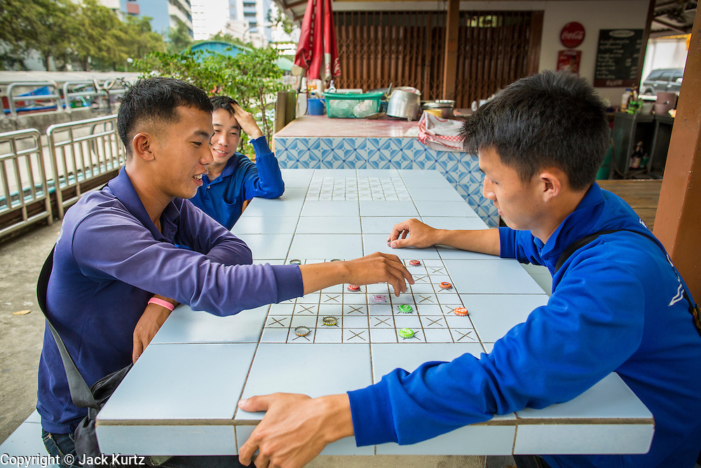 14 NOVEMBER 2012 - BANGKOK, THAILAND: Passenger boat ticket takers and fare collectors play checkers at the Wat Sriboonreung Pier, the southern terminal of the Khlong Saen Saeb boat service. Bangkok used to be criss crossed by canals (called Khlongs in Thai) but most have been filled in and paved over. Khlong Saen Saeb is one of the few remaining khlongs in Bangkok with regular passenger boat service. Boats and ships play an important in daily life in Bangkok. Thousands of people commute to work daily on the Chao Phraya Express Boats and fast boats that ply Khlong Saen Saeb. Boats are used to haul commodities through the city to deep water ports for export.      PHOTO BY JACK KURTZ