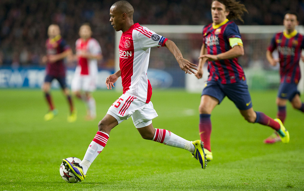 Ajax's Thulani Serero with Barcelona's Carles Puyol during the Group H Champions League soccer match between Ajax and FC Barcelona at the ArenA stadium in Amsterdam, Netherlands, Tuesday Nov. 26, 2013. (AP Photo/Patrick Post)