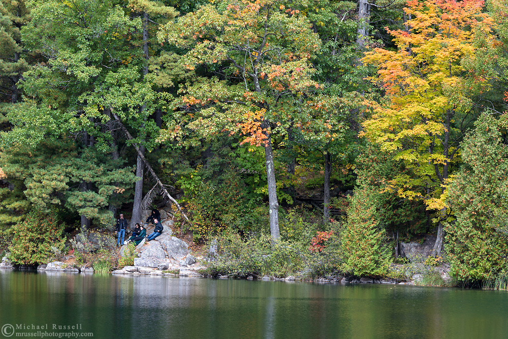 """Hikers relaxing along the shoreline of Pink Lake (Lac Pink) near the Pink Lake Trail.  Photographed during the """"Fall Rhapsody"""" festival celbrating fall foliage colours in Gatineau Park, Québec, Canada."""