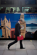 A parked tour coach for Platinum Holidays features famous London landmarks as a businessman walks past checking his smartphone.