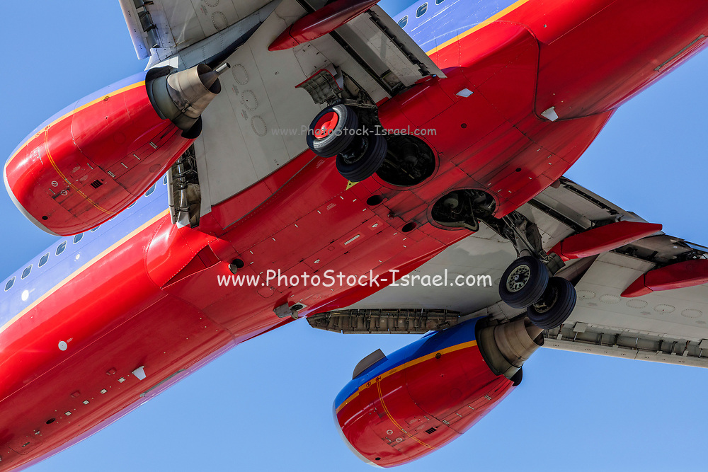 Commercial passenger jet coming in for landing as seen from under the airplane. Landing gear is being lowered