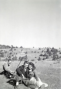 young couple in a field with other man playing in the background