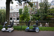 Twee vrouwen vissen, terwijl hun scootmobielen op het fietspad staan.<br /> <br /> Two women are fishing. Their scooters are parked on the bike lane.