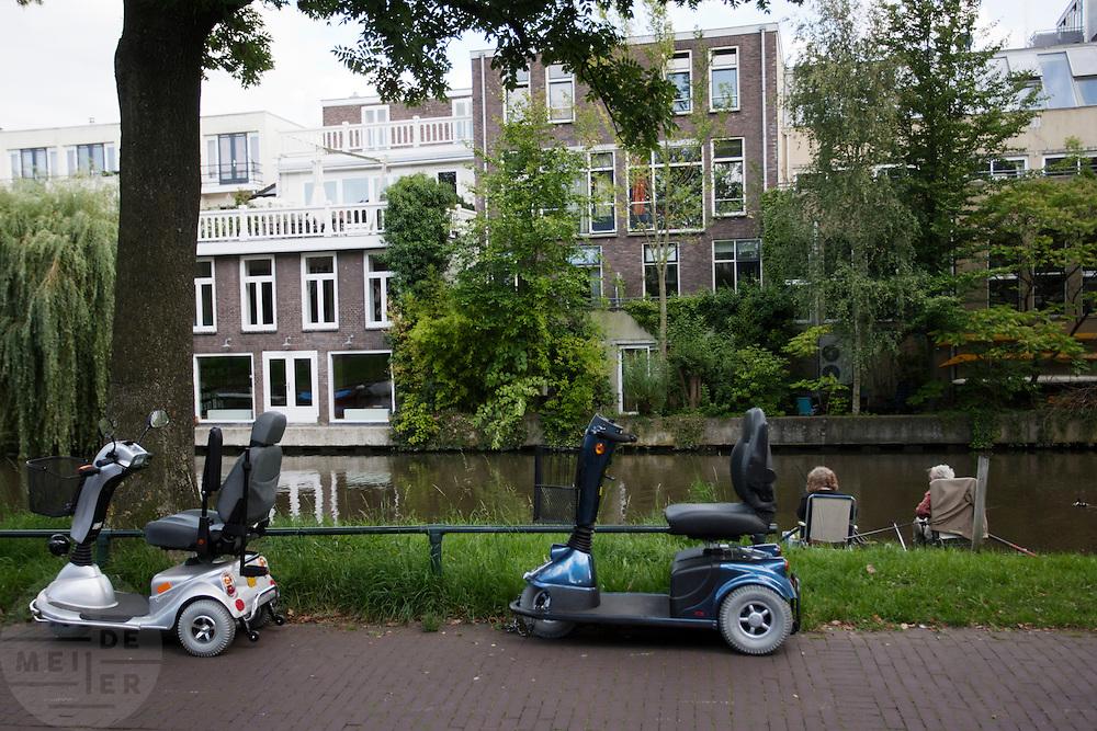 Twee vrouwen vissen, terwijl hun scootmobielen op het fietspad staan.<br /> <br /> Two women are fishing. Their scooters are parked on the bike lane.