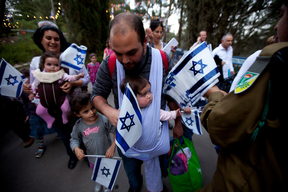 Israeli soldiers hand out Israel's national flags prior to a rehearsal for the main ceremony celebrating Israel's 63rd Independence Day, at Mount Herzl in Jerusalem, on May 5, 2011. Israel will mark its 63rd Independence anniversary of the creation of the state next week.