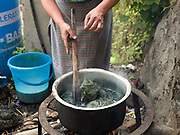 Sonam Wangmo dyeing wild silk with indigo outside her home in Radhi, Eastern Bhutan. Radhi village is famous for fine raw silk and bura textiles made using traditional back-strap loom and natural dyes.