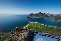 Female hiker enjoys view of beaches and coast from summit of Flakstadtind mountain peak, Flakstadøy, Lofoten Islands, Norway