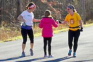 Goshen, New York - Two runners grab cups of water from a young volunteer while competing in the Hambletonian Marathon fun run on Nov. 4, 2012. The run was put together for runners who had trained for the New York City Marathon, which was cancelled because of Hurricane Sandy.