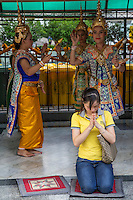 "Erawan Shrine Prayers - Erawan Shrine or ""San Phra Phrom"" in Thai is a Hindu shrine in Bangkok with a statue of the Hindu creation god Brahma or Phra Phrom as it is known in Thai. The shrine features performances by resident Thai dance troupes who are hired by worshippers for making merit.  Erawan Shrine was built in 1956 so as to eliminate the bad karma that was believed to have been caused by laying the foundations of a hotel being built on the wrong date.  The hotel's construction was delayed by a series of troubles: injuries to laborers, budget and the loss of a Italian marble intended for the building. Another dark mark on the location was that Ratchaprasong Intersection had once been used to publicly display and humiliate criminals."