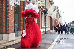 Ascot, UK. 17th June, 2021. Racegoer Debra Day arrives on Ladies Day at Royal Ascot wearing a red dress and large red hat topped by a white swan. Despite Covid restrictions and changeable weather including some rain, many racegoers displayed the elaborate hats and fascinators for which Gold Cup Day has become well known.