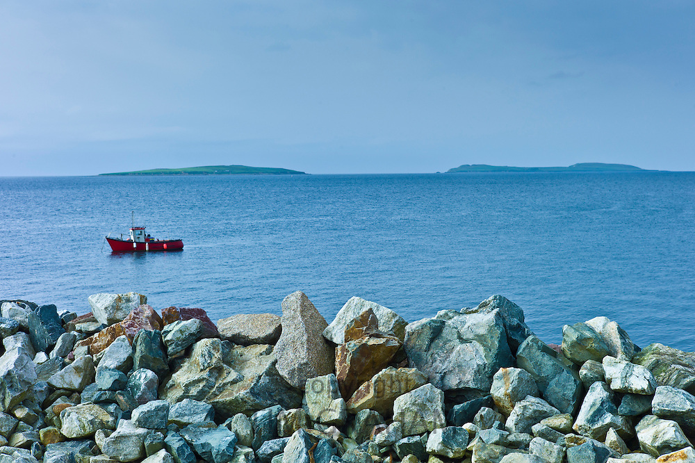 Fishing boat with Saltee Islands in background and sea defences, Kilmore, County Wexford, Southern Ireland