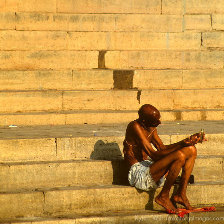 Asia, India, Uttar Pradesh, Varanasi. Scene of daily life along the ghats in the holy city of Varanasi on the Ganges River. A lone man in mediation faces the sunrise.