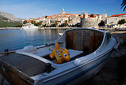 Inflatable dinosaur toy in small wooden boat, Korcula old town in background. Korcula old town, island of Korcula, Croatia
