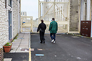 A prisoner accompanied by an officer walking through the prison to visits. HMP/YOI Portland, Dorset. A resettlement prison with a capacity for 530 prisoners. Dorset, United Kingdom.