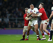 Jonathan Joseph of England is held up by Gareth Anscombe (l) and Steff Evans ® of Wales. England v Wales, NatWest 6 nations 2018 championship match at Twickenham Stadium in Middlesex, England on Saturday 10th February 2018.<br /> pic by Andrew Orchard, Andrew Orchard sports photography