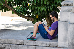 9 September 2015: Student reading on smartphone at the University of Havana, Cuba.
