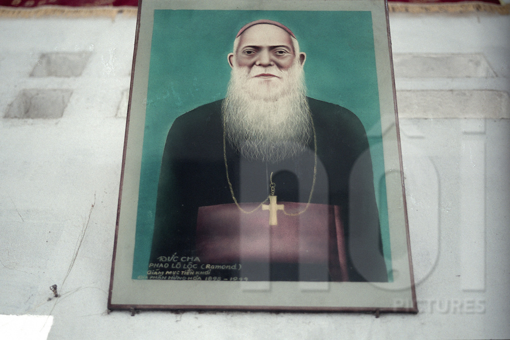 Draw portrait of a vietnamese priest is sticked on a wall. Nam Dinh province, Vietnam, Asia