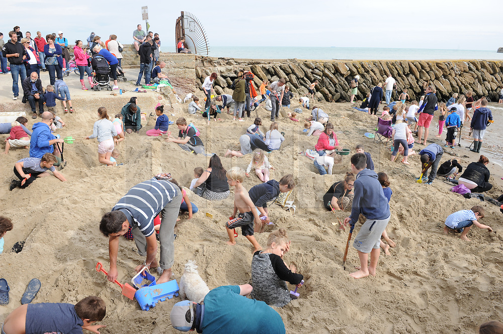 """© Licensed to London News Pictures. 30/08/2014<br /> Folkestone Gold Beach.<br /> £10,000 of buried treasure at Outer Harbour beach near Sunny Sands, Folkestone,Kent.<br /> The installation, entitled """"Folkestone Digs"""", is funded by Bristol-based designers Situations and the idea for the project came from Berlin-based artist Michael Sailstorfer.<br /> The small gold bars - similar to a dog tag - come in two sizes, worth around £250 and £500.<br /> <br /> (Byline:Grant Falvey/LNP)"""