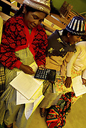 Patacamaya. Women's centre - indigenous women learning accounting and using calculator.