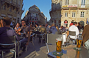 On a cafe terrasse outside seating at sunset with the last rays of sunshine lighting up two refreshing glasses of beer on the Cours de l'Intendance , Bordeaux, Aquitaine, France