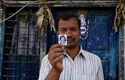 April 26, 2017 - Karnataka, India - Father Shiv Kumar, 32, holding the picture of his six-year-old daughter Harshitha outside his neighbour's residence where his daughter was allegedly raped and murdered, in Veerabhadra Nagar in Bengaluru. Harshitha was missing from four days, was allegedly raped and murdered by her neighbour. After getting foul smell from the neighbour house, the locals alerted police and they recovered the decomposed body of Harshitha under the bed in a cardboard box. (Credit Image: © Cover Asia Press/Cover Asia via ZUMA Press)