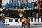 After being trapped underground and broken, a cutting head assembly is finally brought to the surface for repairs, temporarily stopping some workers in their tracks.<br />