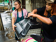28 SEPTEMBER 2015 - BANGKOK, THAILAND:  A couple puts their TV set on the back of a motor scooter while they move out of their home near Wat Kalayanamit. Fifty-four homes around Wat Kalayanamit, a historic Buddhist temple on the Chao Phraya River in the Thonburi section of Bangkok, are being razed and the residents evicted to make way for new development at the temple. The abbot of the temple said he was evicting the residents, who have lived on the temple grounds for generations, because their homes are unsafe and because he wants to improve the temple grounds. The evictions are a part of a Bangkok trend, especially along the Chao Phraya River and BTS light rail lines. Low income people are being evicted from their long time homes to make way for urban renewal.   PHOTO BY JACK KURTZ